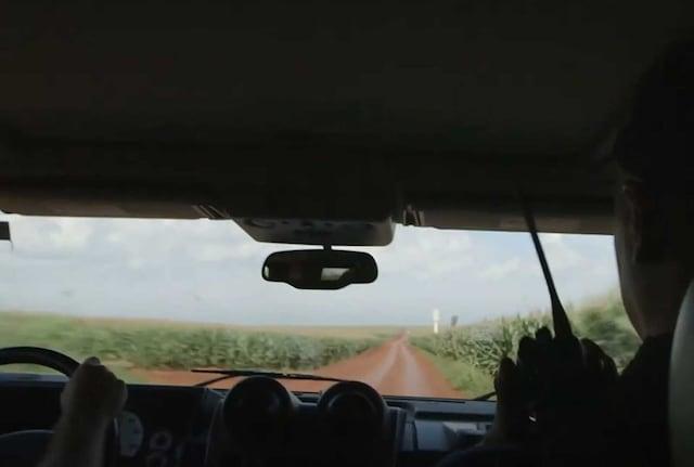 Two men driving through fields