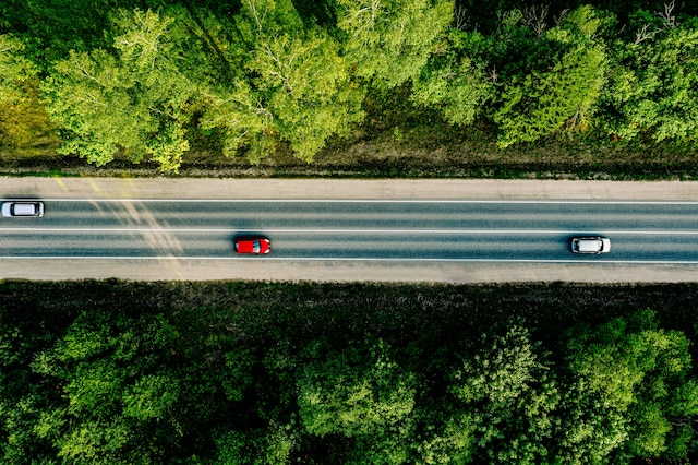 aerial-view-of-cars-driving-through-the-forest-on-XKMJATL