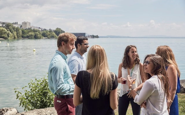 Group drinking and talking by a lake