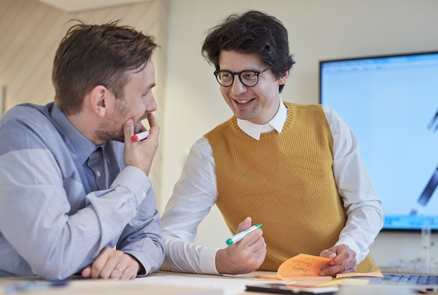 Two PMI employees discussing and smiling