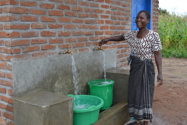 Woman accessing clean water through PMI WASH Initiative