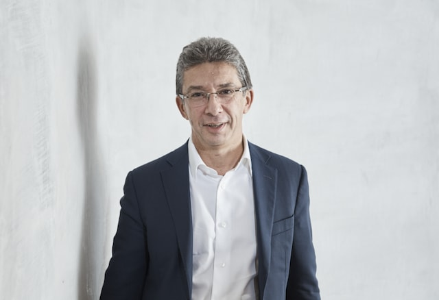 André Calantzopoulos standing by a wall
