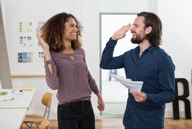 Colleagues laughing and high fiving in office