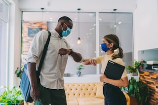 A man and a woman wearing face masks shake their elbows in an office environment.