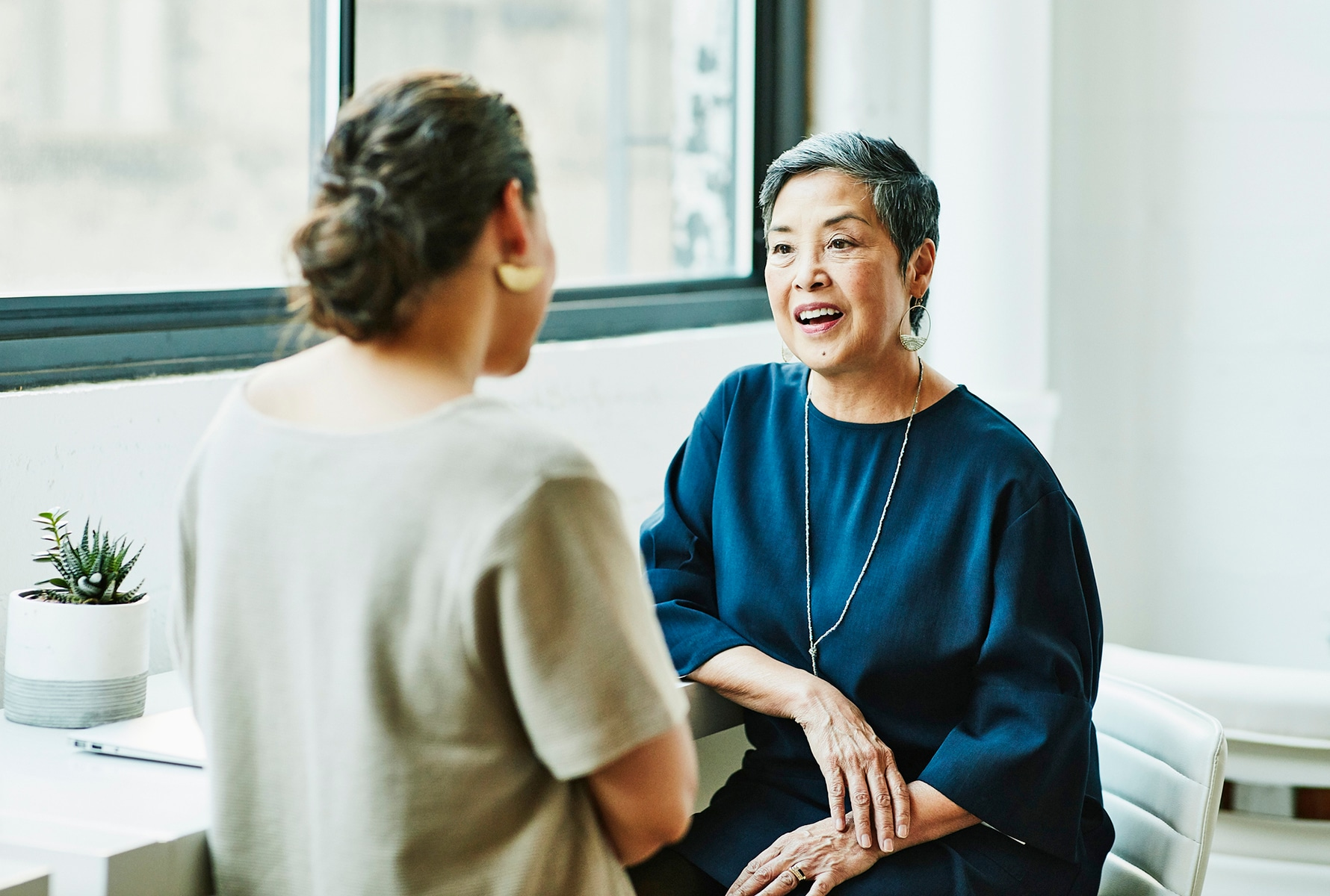 Two women sitting down and talking to each other