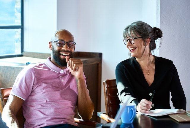 Male and female business coaches laughing together
