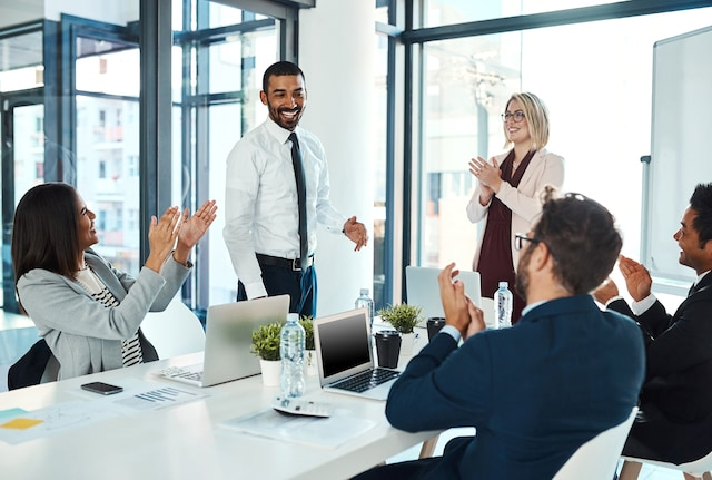 An employee receiving recognition from his team at work