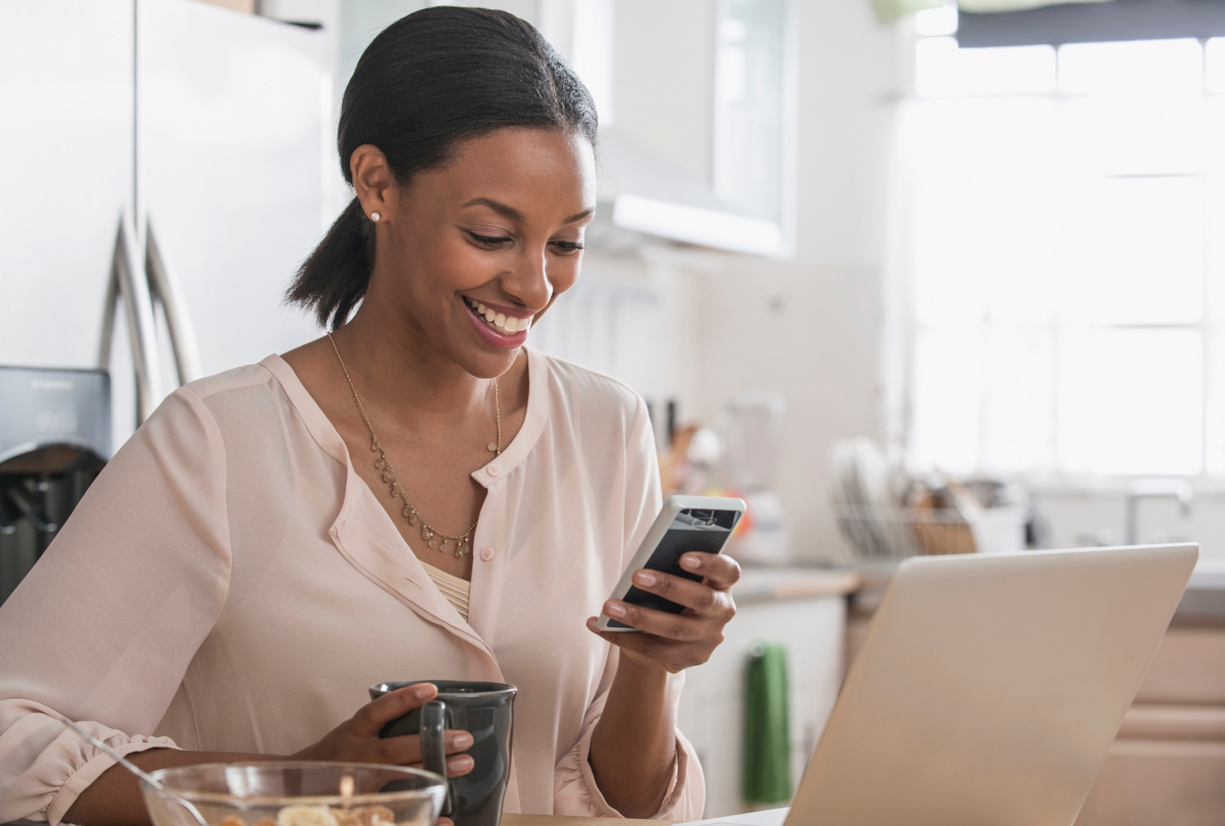 Woman sat in kitchen working smiling at phone