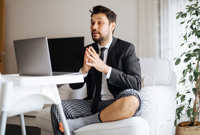 A man wearing a suit and pyjamas working from his sofa