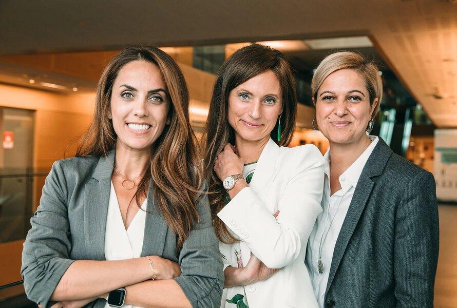 Three women posing in an office environment